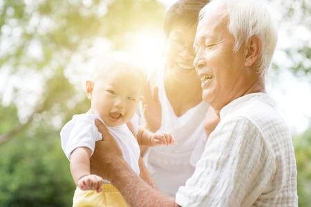Glückliche Großeltern, die mit ihrem Enkel Park am im Freien, asiatische Familie, Lebensversicherungskonzept spielen. Standard-Bild