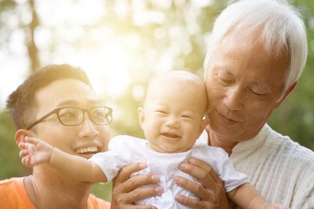 Petit-enfant, père et grand-père de bébé. Famille asiatique multi générations s'amuser en plein air. Concept d'assurance-vie. Banque d'images