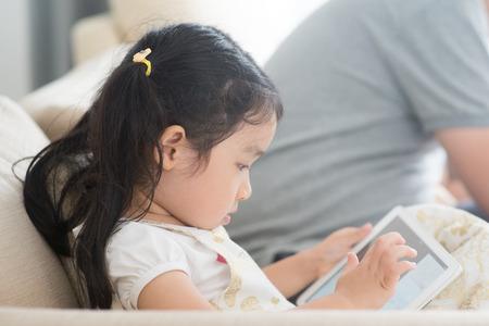 Mała dziewczynka za pomocą cyfrowego tabletu na kanapie. Azjatycka rodzina w domu, życie w domu.
