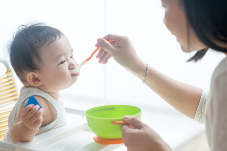 Famiglia asiatica felice a casa. Generi l'alimento solido dell'alimento al neonato di 9 mesi nella cucina, stile di vita vivente all'interno. Archivio Fotografico - 97097014