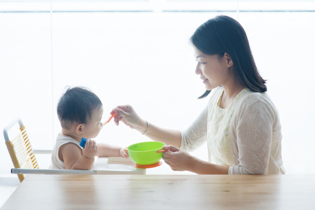 Happy Asian family at home. Mother feeding solid food to 9 months old toddler in the kitchen, living lifestyle indoors.  Stock Photo