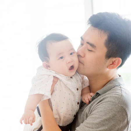 Happy Asian family at home. Father kissing baby boy, living lifestyle indoors.