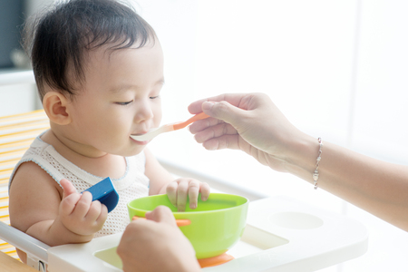 Happy Asian family at home. Mother feeding solid food to 9 months child in the kitchen, living lifestyle indoors.