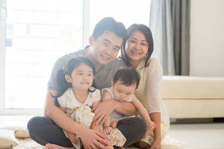Parents and children sitting on floor together. Happy Asian family spending quality time at home, natural living lifestyle indoors.