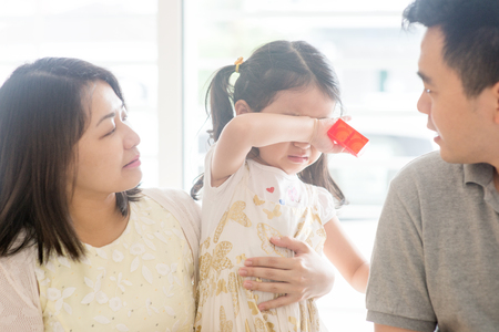 Parents comforting crying daughter. Asian family at home, natural living lifestyle indoors.