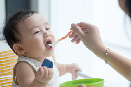 Happy Asian family at home. Mother feeding solid food to 9 months old son in the kitchen, living lifestyle indoors.  Stock Photo