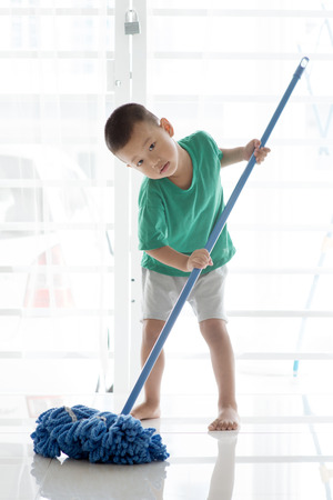 Asian boy cleaning floor with mop. Young child doing house chores at home.