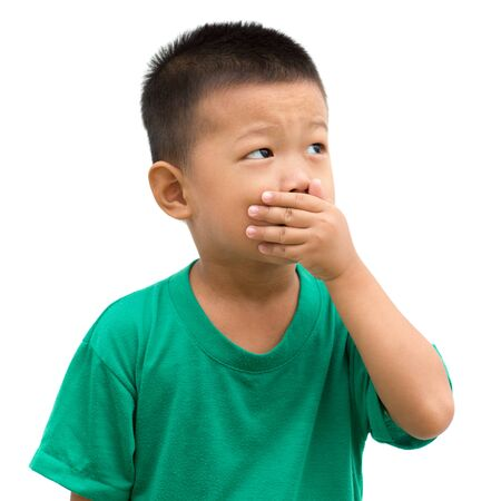 Asian child covering his mouth and looking to side. Portrait of young boy isolated on white background.