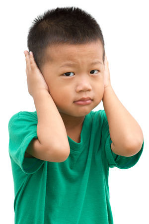 Asian child covering his ears with hands. Portrait of young boy isolated on white background.