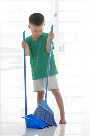 Asian boy sweeping floor with broom. Young child doing house chores at home. Stockfoto