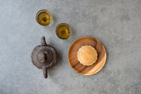 Traditional baked mooncakes is offered to friends or family during Mid-Autumn Festival. Flatlay on table top down view grey background with copy space. The Chinese character on the moon cake represent