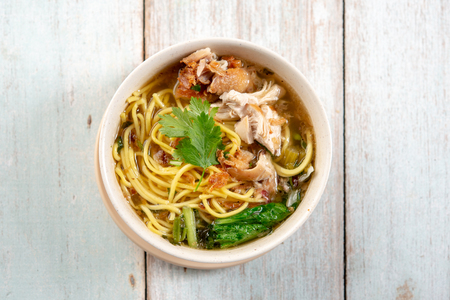 Asian soup noodles and chicken in bowl on wooden background. Top view flat lay. Foto de archivo