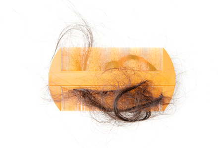 Hairloss problem. Flat lay top view comb with lost hair on it, isolated on white background. Foto de archivo