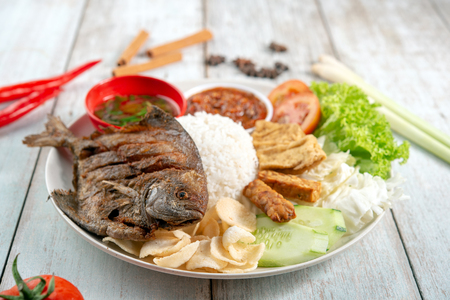 Fried pomfret fish and rice, popular traditional Malay or Indonesian local food.