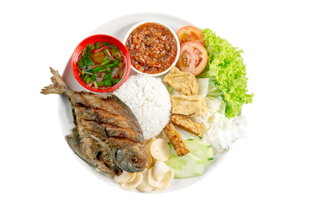 Fried pomfret fish and rice, popular traditional Malay or Indonesian local food. Isolated on white background. Flat lay top down overhead view. Stockfoto