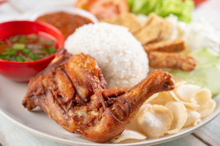 Nasi lemak kukus with fried drumstick, popular traditional Malaysian local food.