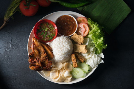 Nasi lemak kukus with fried chicken, popular traditional Malaysian local food. Flat lay top down overhead view.