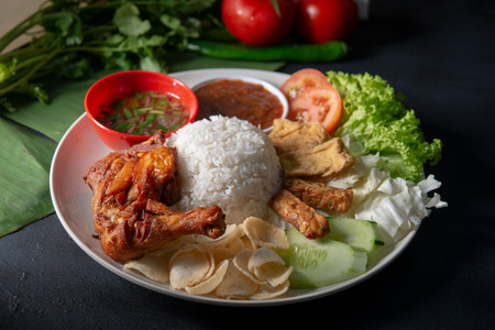 Nasi lemak kukus with fried drumstick, popular traditional Malaysian local food.