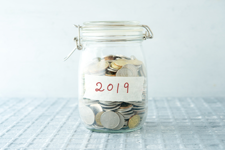 Coins in glass money jar with 2019 label, financial concept. Reklamní fotografie