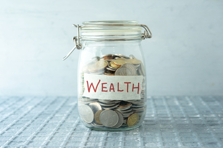 Coins in glass money jar with wealth label, financial concept.