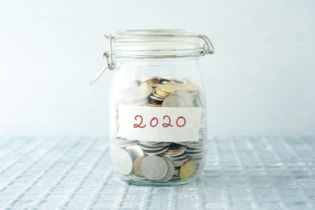 Coins in glass money jar with 2020 label, financial concept.