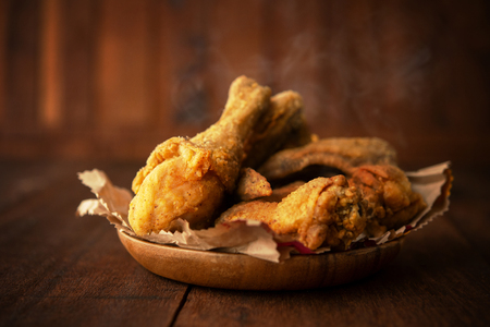 Plate of original recipe fried chickens, on dark wooden background.
