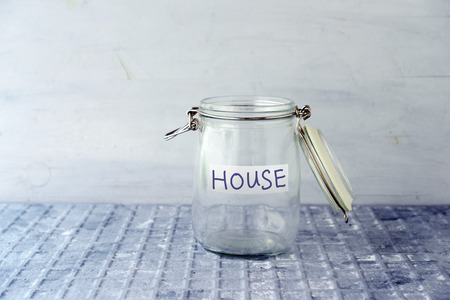 Empty glass money jar with house label, financial concept.
