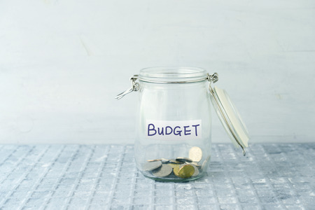 Little coins in glass money jar with budget label, financial concept.