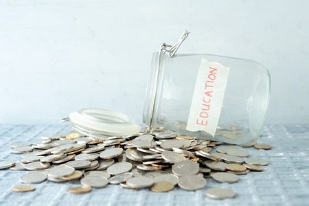 Coins and glass money jar with education label, financial concept.