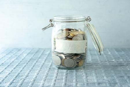 Monedas en tarro de dinero de cristal con etiqueta en blanco, concepto financiero.