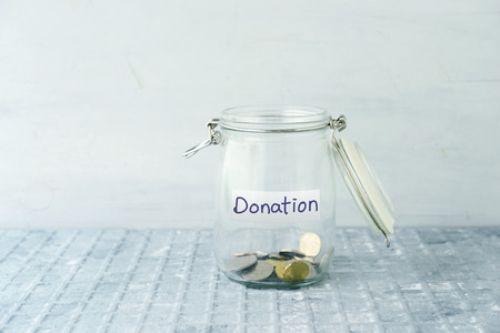 Coins in glass money jar with donations label, financial concept.