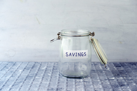 Empty glass money jar with savings label, financial concept. Banque d'images