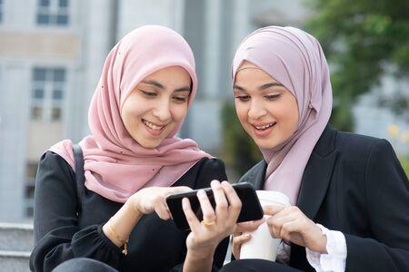 Muslim women using smart phone, sharing and laughing.