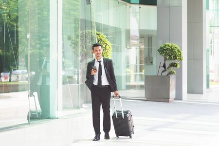 Busy Asian businessman with luggage walking to airport, checking schedule from smartphone.