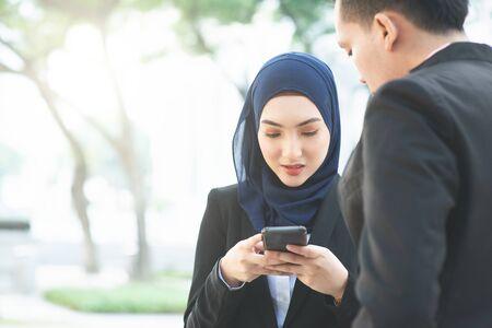 Muslim business women using mobile phone outdoor.