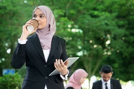 Muslim business woman drinking coffee while going to work in morning. Imagens