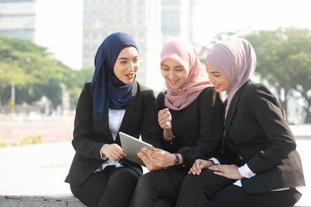 Group of Muslim business women discussing, using tablet pc outdoor. Stockfoto