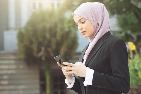 Muslim business woman walking and using smart phone.