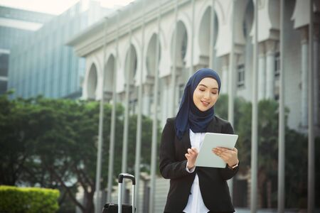 Muslim woman working on table pc outdoor, business travel concept. Stock Photo