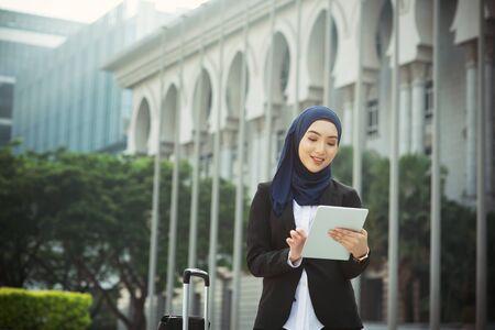 Muslimische Frau, die am Tisch-PC im Freien arbeitet, Geschäftsreisekonzept.
