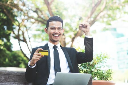 Happy Asian business man cheering, hand holding credit card sitting with laptop outdoor. Archivio Fotografico