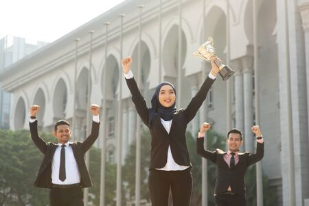 Muslim businesswoman holding a trophy, woman power in business, top performance concept.