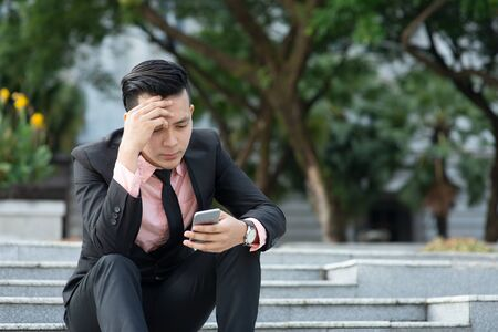 Man looking at mobile phone with serious face, negative emotion, phishing scams concept.