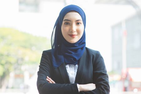 Portrait of Muslim woman in business suit, arms crossed and smile looking at camera.