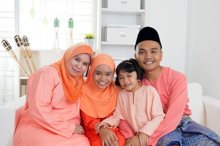Happy Malay family portrait in traditional clothing during Hari Raya. Malaysian family lifestyle at home. Imagens