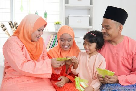 Woman giving green packet to the girls during hari raya. Malay or Malaysian family lifestyle at home.