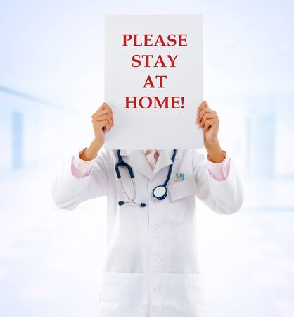 Medical staff holding a card with stay at home on it.
