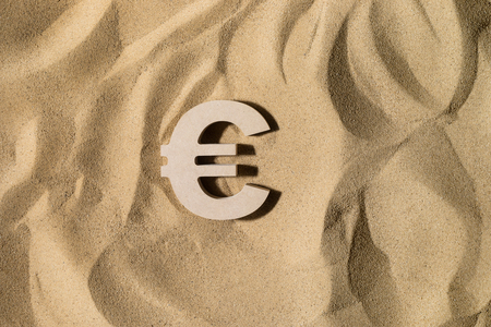 Euro Symbol lies on the Sand in Direct Sunlight