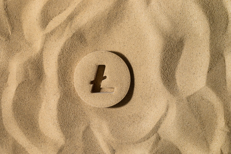 Litecoin Symbol or Sign Covered with Sand in the Sun after Crisis Stock Photo