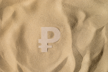Russian Ruble Symbol lies on the Sand in Direct Sunlight
